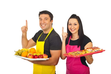 selling points: Grocery workers pointing up to copy space and holding plateau with fruits and cakes isolated on white background