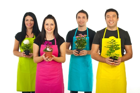 Team of four gardeners workers in colorful aprons offering flowers pots isolated on white background photo