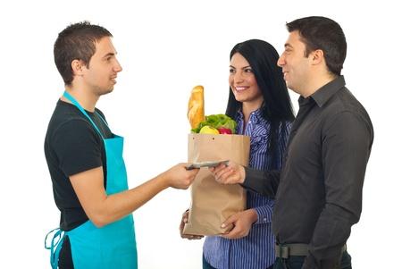 oficinista: Pareja pagando con dinero banknoted sus alimentos en el mercado a hombre cajero aislado sobre fondo blanco Foto de archivo