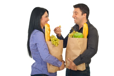 Laughing couple having conversation and holding shopping bags with food isolated on white background photo