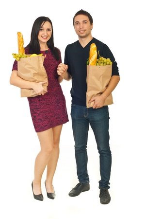 Young couple holding hands and shopping bags with food isolated on white background photo