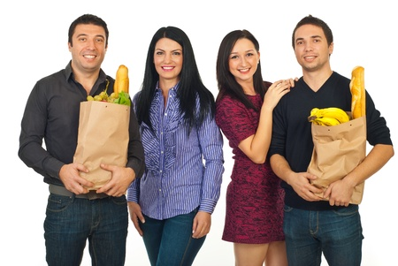 Group of four cheerful friends with shopping bags with food isolated on white background photo