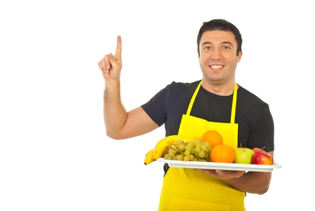 Smiling fruiterer holding fruits and pointing upwards isolated on white background photo