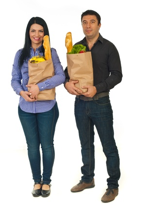 Full length of couple holding paper shopping bags with food isolated on white background photo
