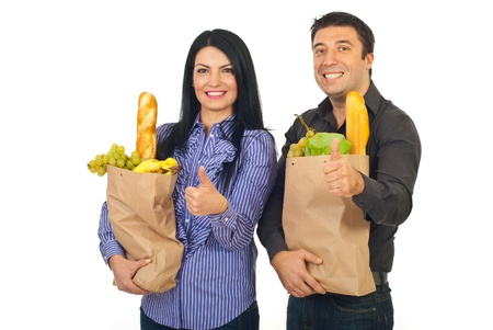 Successful happy family holding paper shopping bags with food and giving thumbs up isolated on white background photo