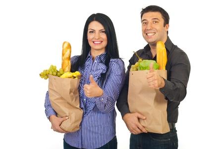 Succesvolle gelukkige familie bedrijf papier boodschappentassen met voedsel en het geven van thumbs up op witte achtergrond