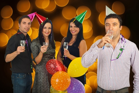Cheerful friends celebrating New Years Eve party and holding glasses with champagne over background with Christmas lights photo