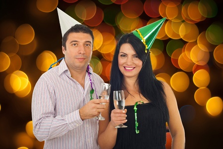 Couple celebrating New Years Eve with lights around them and toasting with champagne photo
