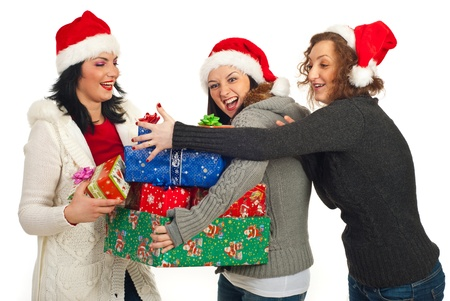 three gift boxes: Happy friends women having fun with Christmas gifts isolated on white background