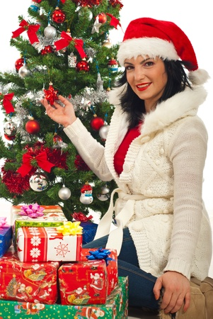 Happy woman sitting near Christmas tree with stack of gifts  photo