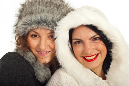 Close up of two happy women friends wearing fur hats isolated on white background photo
