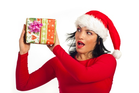 Surprised woman with santa hat holding Christmas present and looking  to box isolated on white background photo