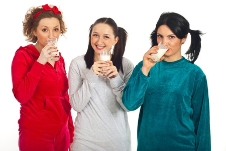 Three happy friends women in pajamas drinking milk isolated on white background photo
