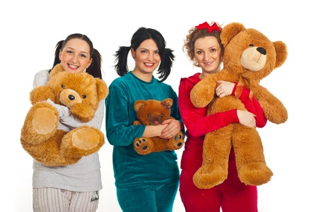pyjamas: Three women in pyjamas holding teddy bears and smiling isolated on white background