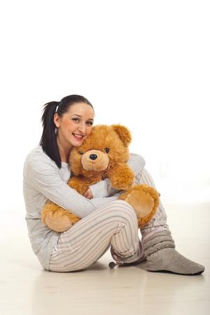 cola mujer: La mujer en pijama sentado en el suelo y abrazando el oso de peluche Foto de archivo