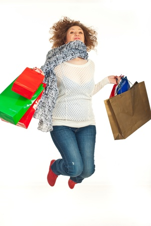 Cheerful redhead woman leaping with shopping bags isolated on white background photo