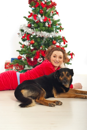 Happy woman with her dog lying down on floor by Christmas tree photo