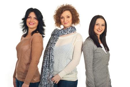 Mooie glimlachende drie vrouwen vrienden staan in een lijn geïsoleerd op witte achtergrond