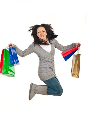 Excited woman jumping with her shopping bags isolated on white background Stock Photo