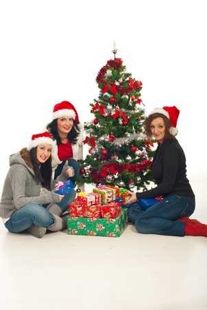 three gift boxes: Cheerful three women celebrating Christmas and holding presents Stock Photo