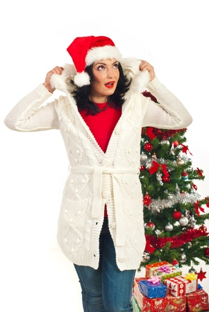 Surprised Santa helper woman in winter clothes looking up and holding her fur hood against white background photo
