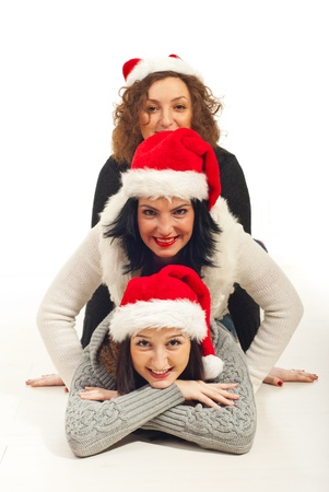 pullovers: Happy three friends with Santa hat lying on top each other on floor and having fun