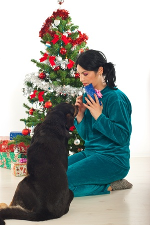 Woman sharing Christmas gift with her dog and having conversation near tree photo