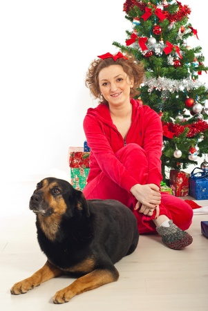 Smiling woman in red pyjamas sitting on floor with her dog near Christmas tree photo