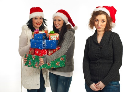 Sad woman standing alone without presents while her friends smiling and holding many Christmas presents  isolated on white background photo