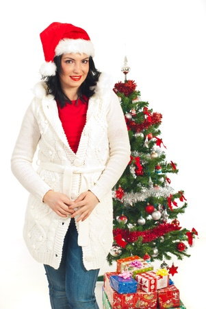 Attractive woman with Santa hat standing near Christmas tree with presents isolated on white background photo