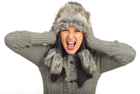 Crazy winter woman holding head in fur hat and screaming isolated on white background photo