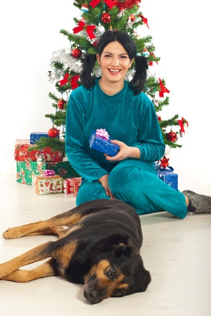 Laughing woman in pajamas sitting on floor with her dog near Christmas tree photo