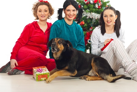 Group of three women on pajamas  with their dog sitting near Christmas tree in home photo