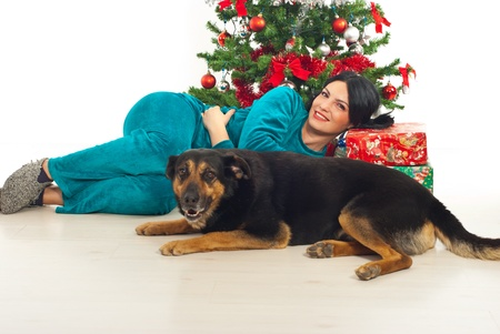 Smiling woman and her dog lying on floor near Chrostams tree with gifts photo