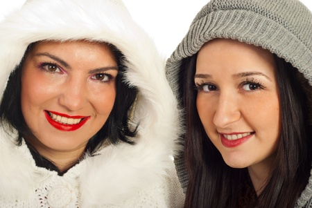 Close up of two women friends in woolen hoods isolated on white background photo