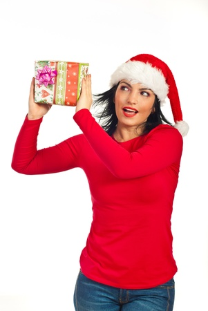 Happy amazed woman with Santa hat holding Christmas gift isolated on white background photo