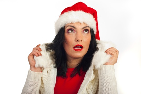 Amazed winter woman with Santa hat looking up and holding her fur jacket against white background photo