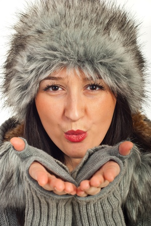 Close up of beauty winter woman in grey fur hat blowing  photo