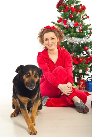 Happy woman in pyjama  and her  funny dog sitting on floor near Christmas tree photo