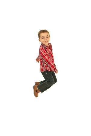 Joyful little boy jumping in the air isolated on white background Stock Photo - 12595112