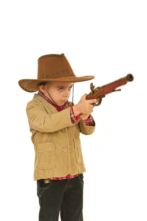 Small cowboy boy with hat playing with gun toy isolated on white background photo