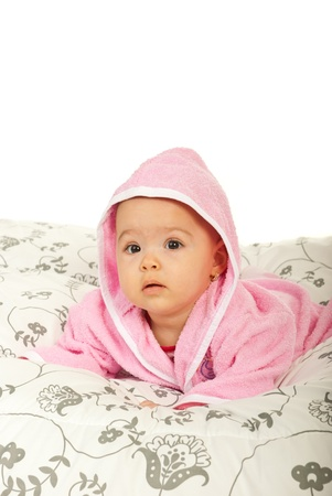 Baby girl in bathrobe lying on belly  in bed and looking at you with surprised face against white background photo