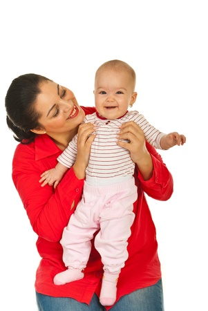 Happy mother holding and looking at her laughing baby girl against white background photo