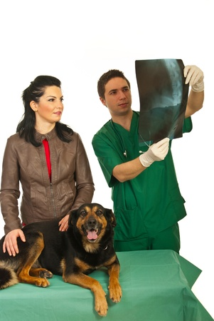 Owner woman with her dog having conversation with vet man and together looking on spine dog x-ray photo