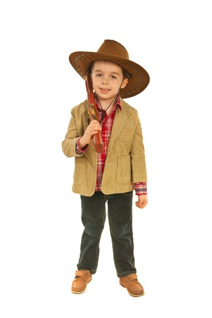 Relaxed little smiling cowboy resting his gun on shoulder isolated on white background photo