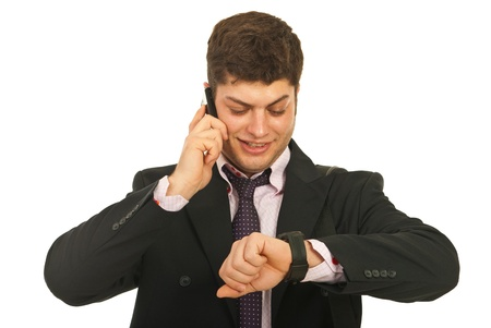 Happy business man speaking by phone mobile and  looking at his watcg isolated on white background Stock Photo - 12595205