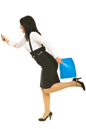 Stressed business woman  in a hurry holding phone mobile , folders and  being surprised of her late isolated on white background photo