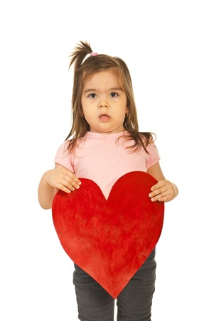 Serious toddler girl holding a big heart isolated on white background photo