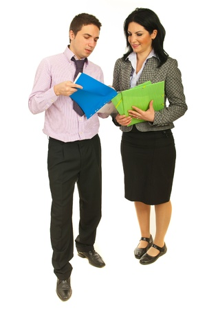 two people talking: Full length of two business people looking on contracts and having conversation isolated on white background
