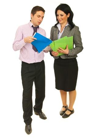 Volledige lengte van twee mensen uit het bedrijfsleven op zoek op contracten en het hebben van een gesprek geïsoleerd op witte achtergrond